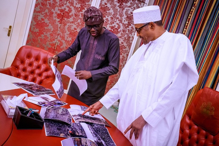 Babajide Sanwo-Olu shows pictures to Buhari.